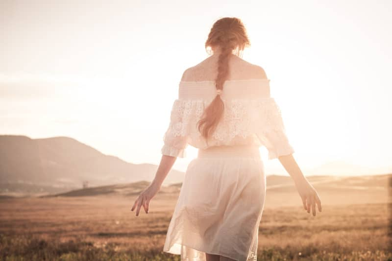 woman walking in a field | article on 3 Ways to Experience God's Rest