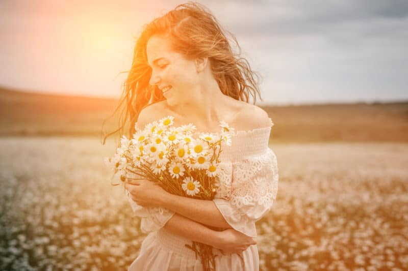 smiling young woman with armful of daisies | article on 3 Ways to Experience God's Rest