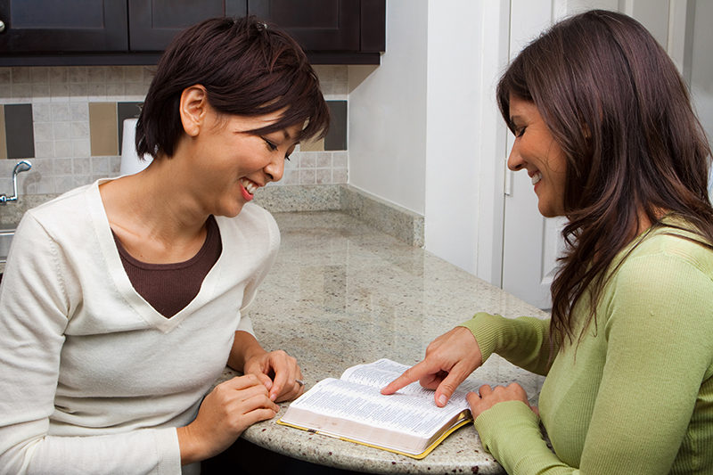 Two christian women studying the Bible together in the kitchen | Free Bible Study Challenge at LivingbyDesign.org