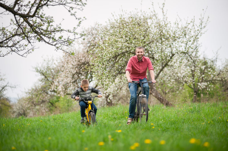 happy father and son riding their bikes in the park together | Article on Fostering Healthy Independence in Your Children