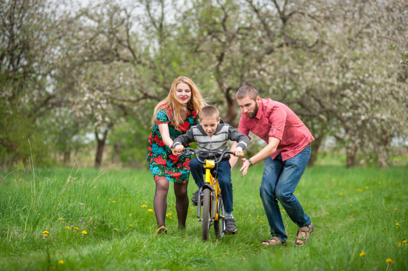 parents teaching their son how to ride his bike for the first time | Article on Fostering Healthy Independence in Your Children