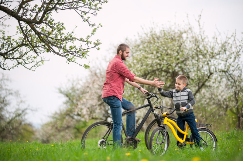 father and son giving high fives to each other on their bikes | Article on Fostering Healthy Independence in Your Children