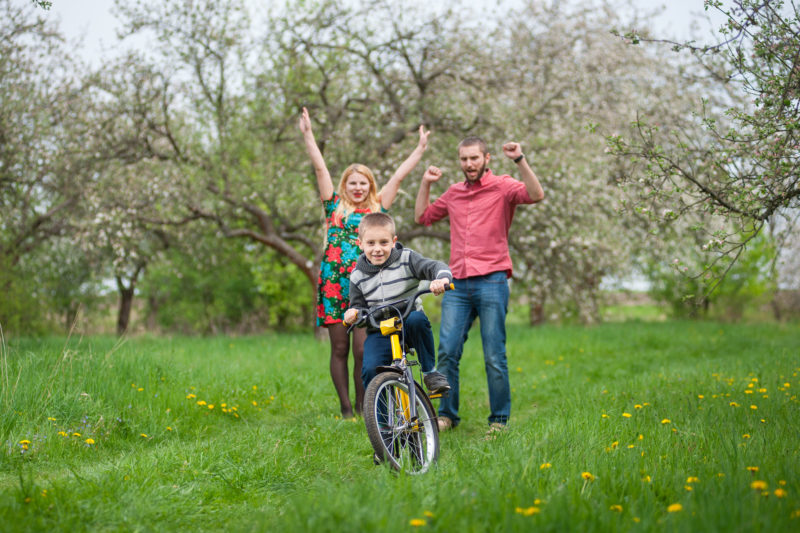 parents cheering as a young boy rides his bike alone for the first time | Article on Fostering Healthy Independence in Your Children