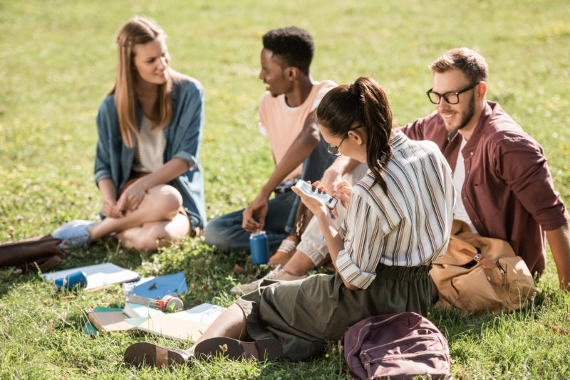 group of young people sharing their faith with friends in a park | article on Sharing the Gospel in a Postmodern World