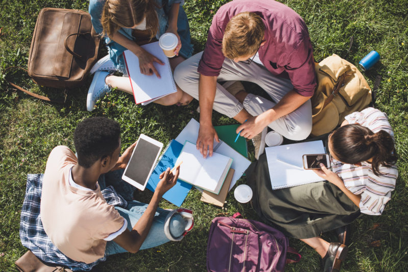 group of young people sharing their faith and studying the Word together in a park | article on Sharing the Gospel in a Postmodern World