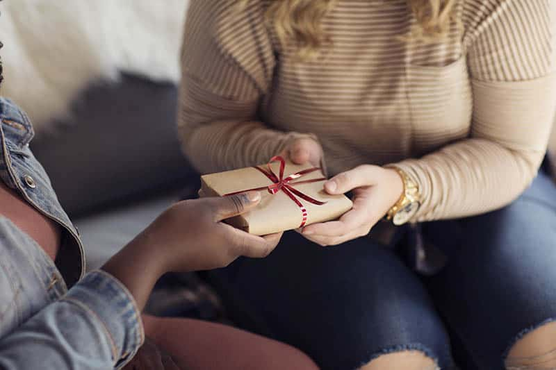 Christian woman giving a generous holiday gift   Double your impact this giving season