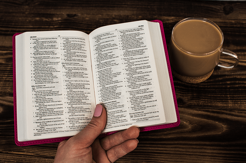 Woman holding a Bible open to the old testament | Three Reasons the Old Testament is Still Relevant