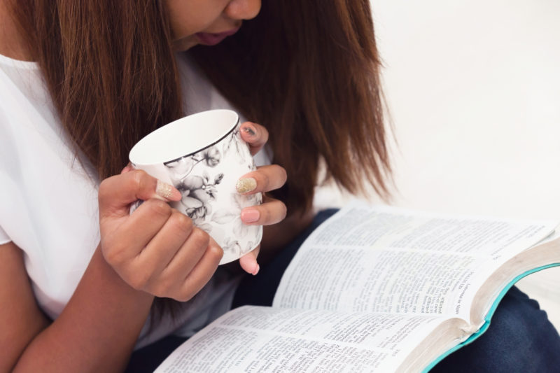close up of woman holding a cup of coffee as she studies her Bible | What is theology & Why does it matter?