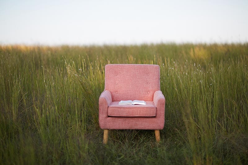 Open bible sitting on a chair in a field | Dwell in God's Word