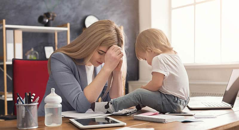 Christian woman praying for flexibility while her child plays on her desk