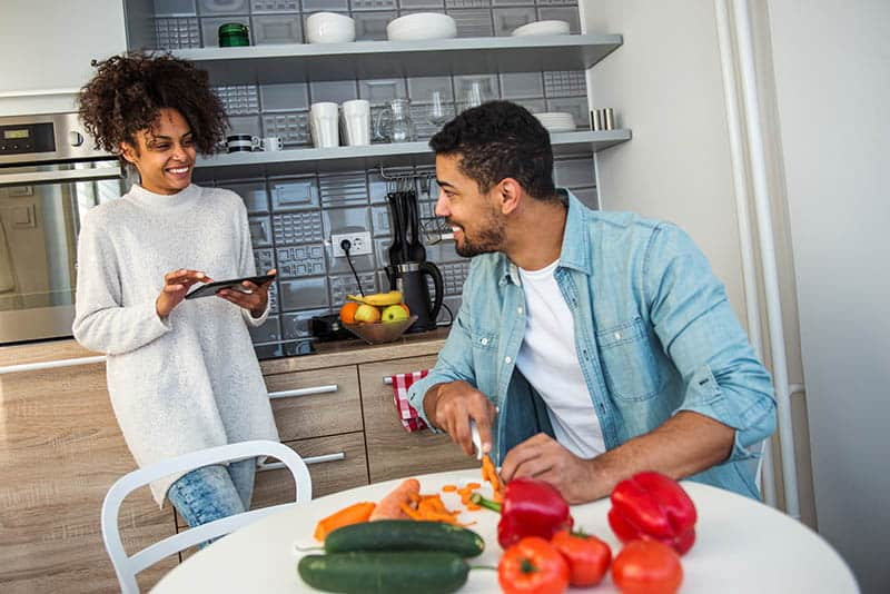 Christian Woman choosing to dwell on God's Word in the Kitchen while her husband cuts vegetables.