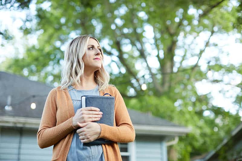 A Christian Woman holding her Bible outdoors | What do you believe about the Bible?