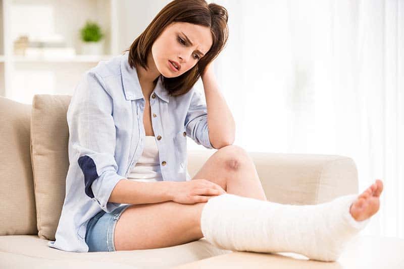 frustrated woman sitting on the couch with broken leg | Do you want to get well?
