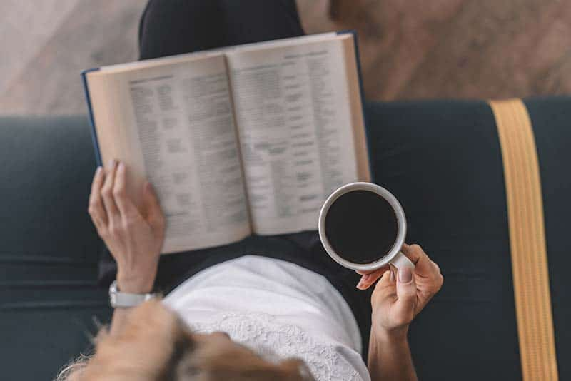 Christian woman drinking coffee and studying her Bible | How Can a Good God Allow Suffering?