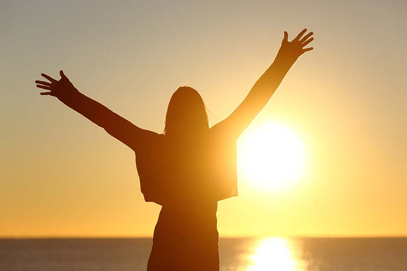 Free happy woman raising arms watching the sun in the background at sunrise | How Can a Good God Allow Suffering?
