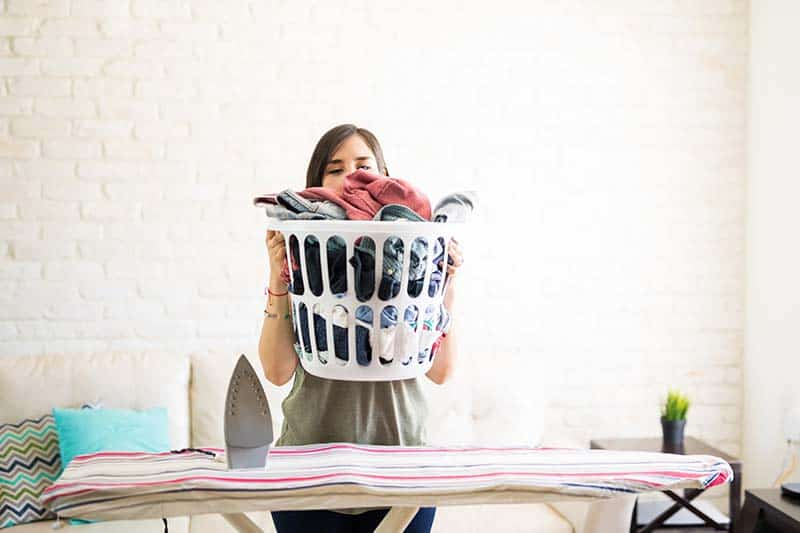 Housewife covering face with heavy laundry basket and keeping on iron table | How to Replace the World's Lies with God's Truth