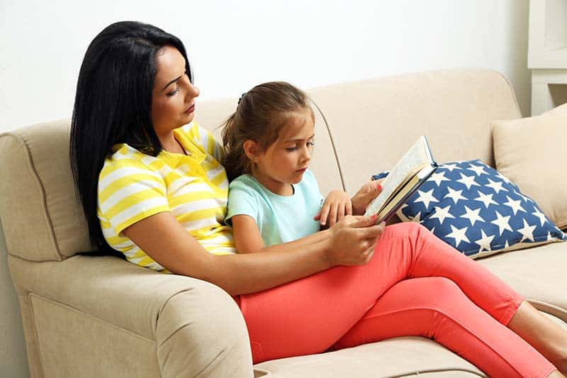Beautiful little girl reading book with mother on sofa at home | How to Replace the World's Lies with God's Truth