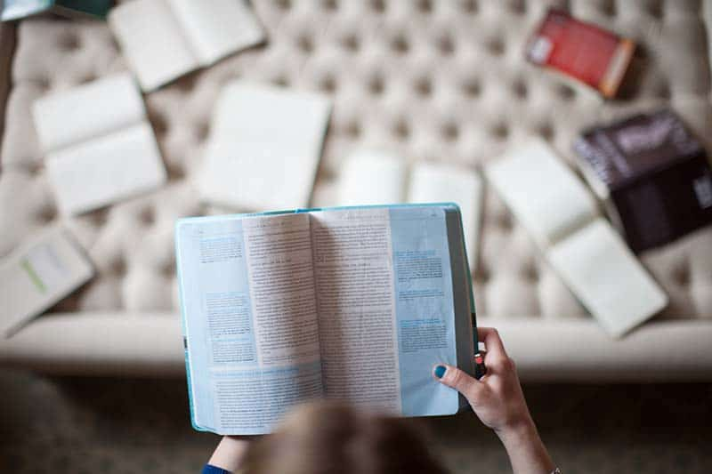 Woman holding a bible looking down at a couch full of study tools for her daily bible study routine