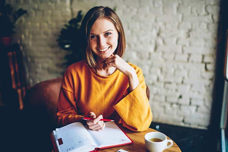 beautiful cheerful Christian woman with stylish short haircut smiling at camera making notes in notebook during her daily bible study routine