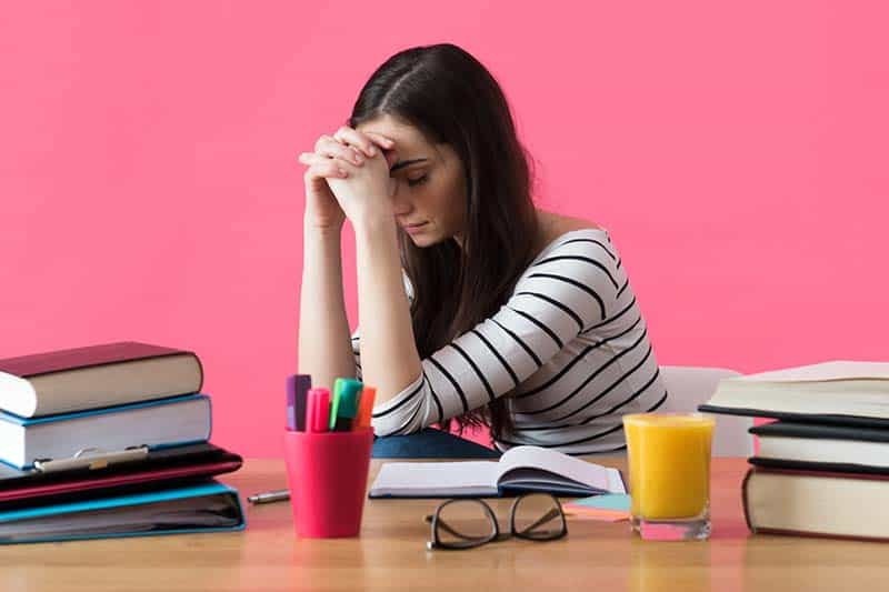 Frustrated Christian woman with desperate expression sitting at her desk praying. | 5 Practical Ways to Combat Bible Study Frustrations