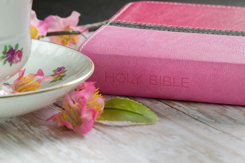 A Pink Holy Bible on a wood plank board with a cup of coffee or tea surrounded by pink spring flowers | 5 Practical Ways to Combat Bible Study Frustrations