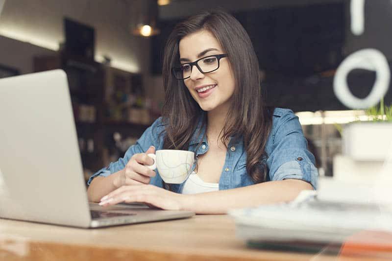 Beautiful Christian woman using laptop at cafe