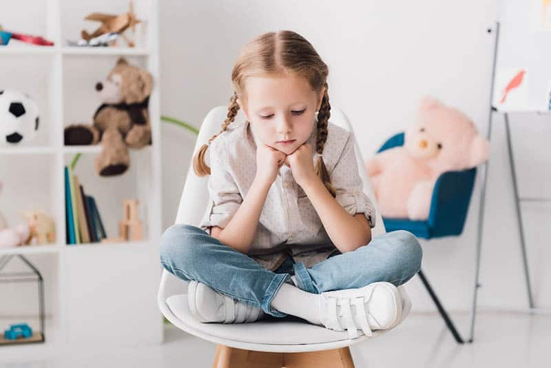 young girl struggling with complicated emotions sitting on a chair in her room with a sad look on her face