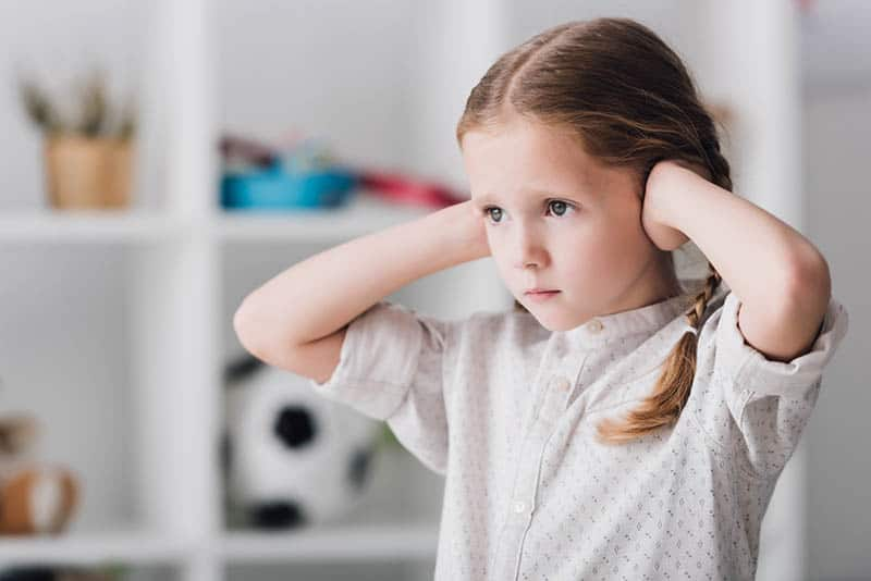 young girl covering her ears with an anxious look on her face, kids navigate emotions