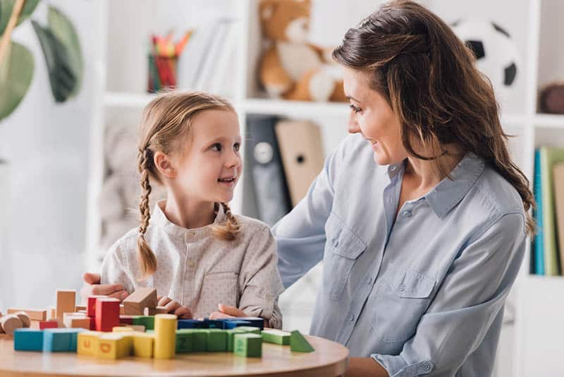 Christian mom playing blocks with her young daughter who is smiling
