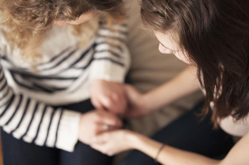 Two christian women prayer partners praying together on the couch.