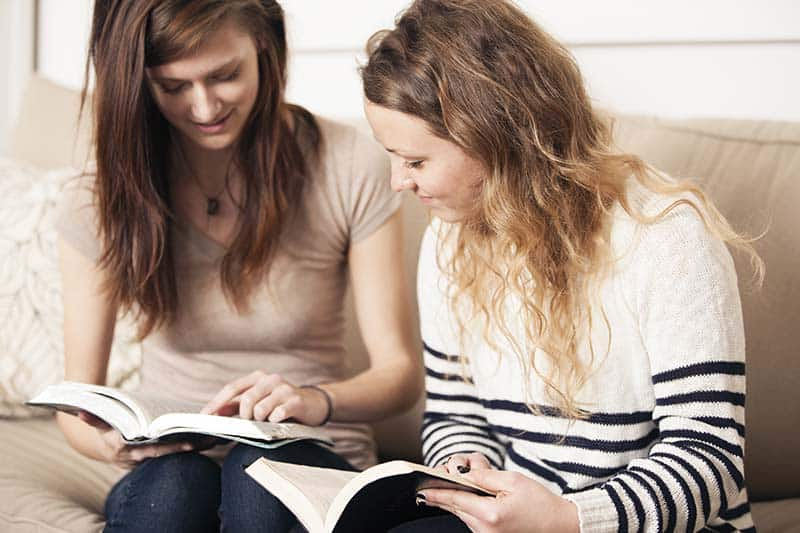 Christian girls studying their Bibles together and helping each other as prayer partners