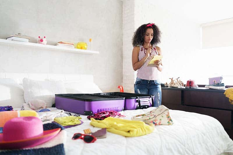 Young black woman packing bags for holiday. Girl preparing suitcase for vacation, looking at checklist to get ready for travelling