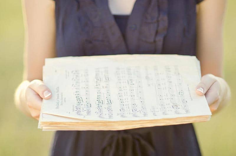 Christian woman holding sheet music  | Free hymn-inspired Bible study