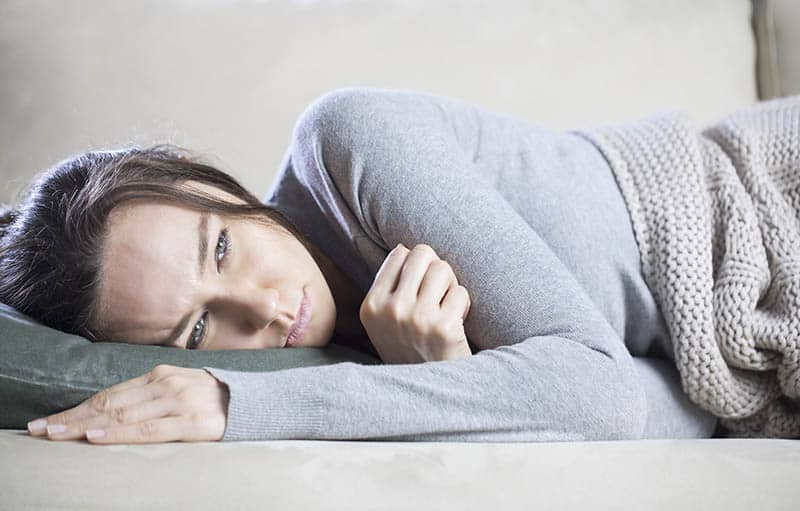 Young Christian woman laying in bed battling depression