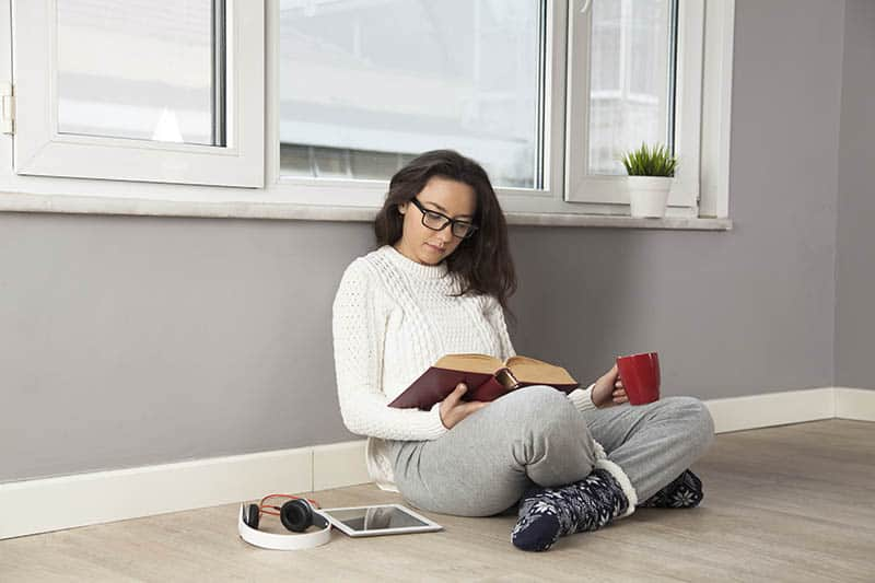 young woman reading the Bible while sitting on the floor at home battling depression.