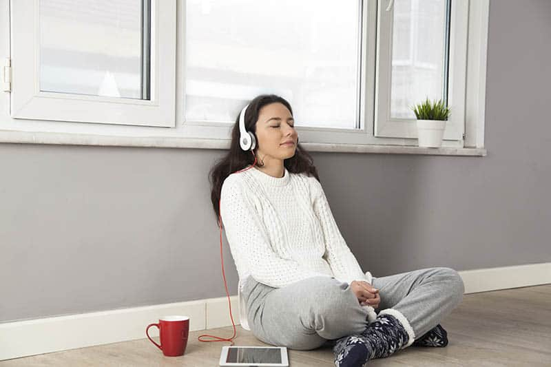 Young woman listening to an audio Bible while sitting on the floor at home battling depression.