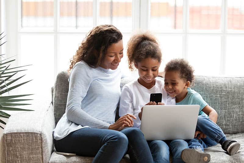 Young black family sit on couch at home using devices playing game on smartphone.  Embracing the Silence