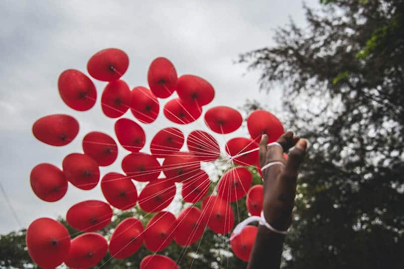 Woman' s hand holding red balloons | God Can Renew Your Hope & Restore Your Wasted Years