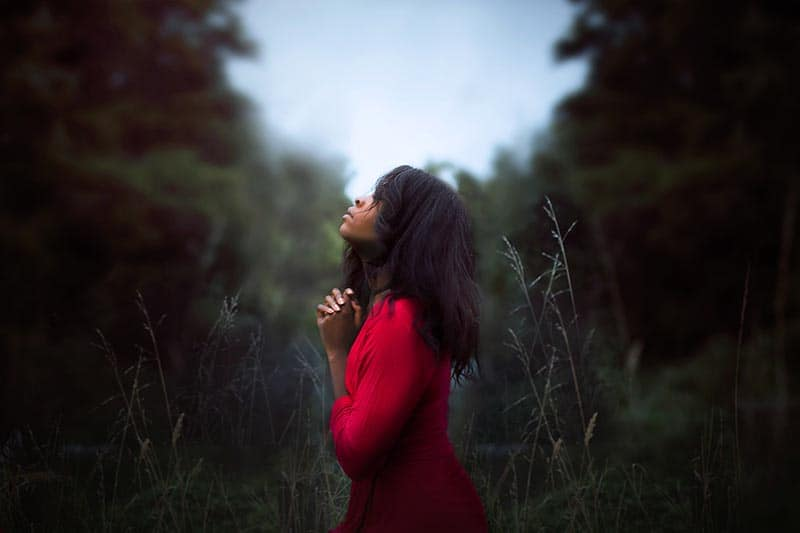 Sad woman praying in a field | God Can Renew Your Hope & Restore Your Wasted Years