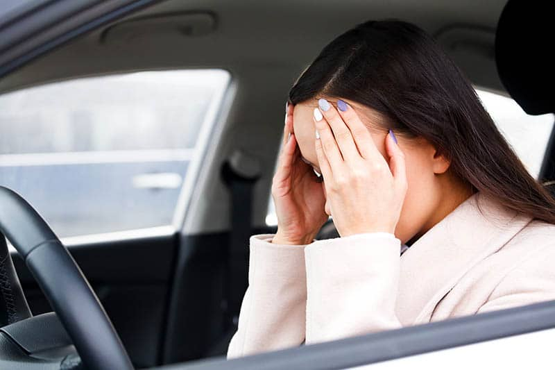 Young depressed woman driver holding head in hands | Anti-Anxiety Toolbox for Women
