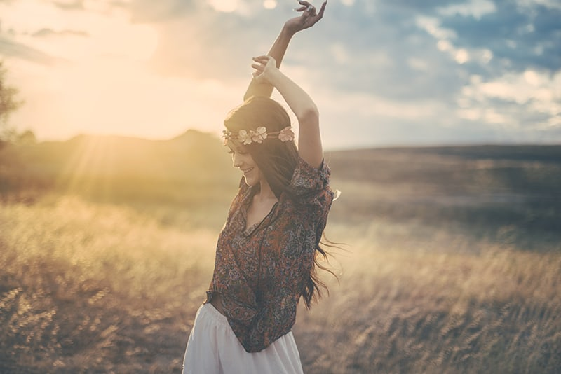 joyful Christian woman in a field at sunset