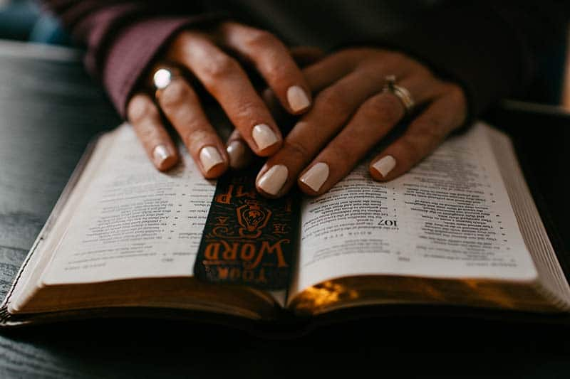 christian woman's hands placed on top of Scripture