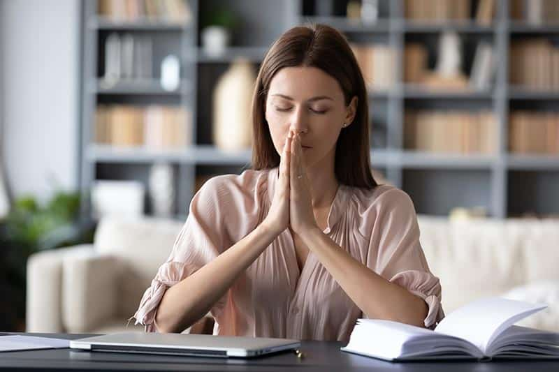 Christian woman praying against anxiety before she begins her work day | Anti-Anxiety Toolbox