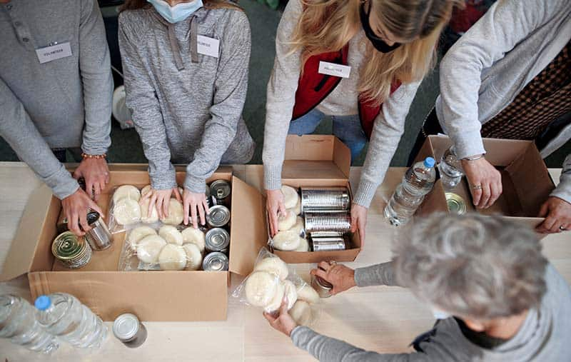 Top view of group of volunteers working in community charity donation center | prevent exhaustion while serving others