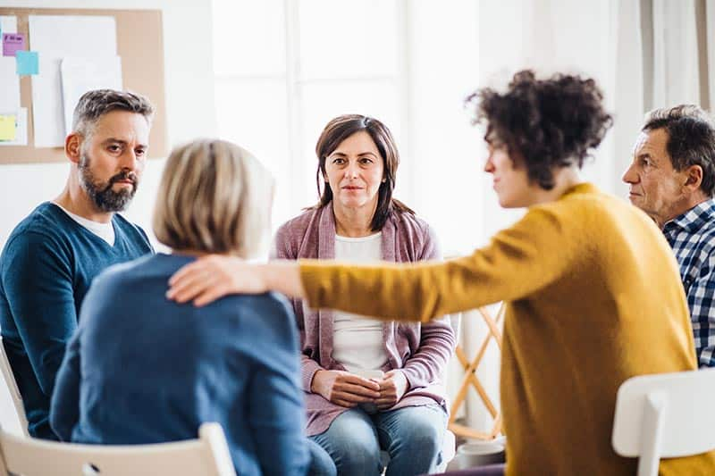 men and women sitting in a circle during group therapy, supporting each other | prevent exhaustion while serving others