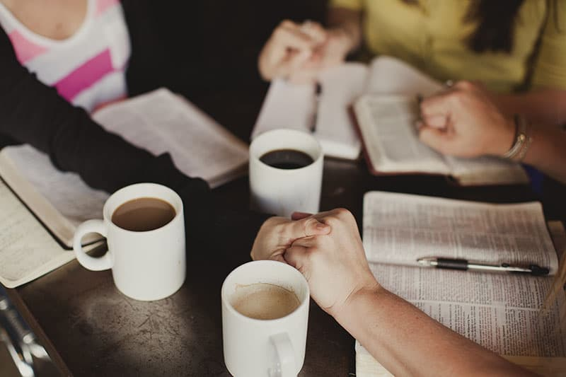 Christian women holding hands and praying together with open bibles and hot coffee