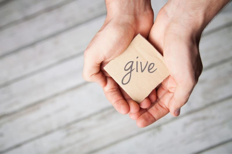 woman's hands holding a note that says give | fundraiser to cover the cost of our free bible study resources