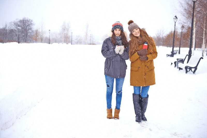 Two women out in the snow holding warm beverages  | 5 ways to battle Christian complacency
