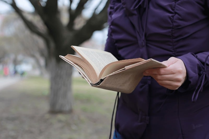 woman reading book outside by a tree  | 5 ways to battle Christian complacency