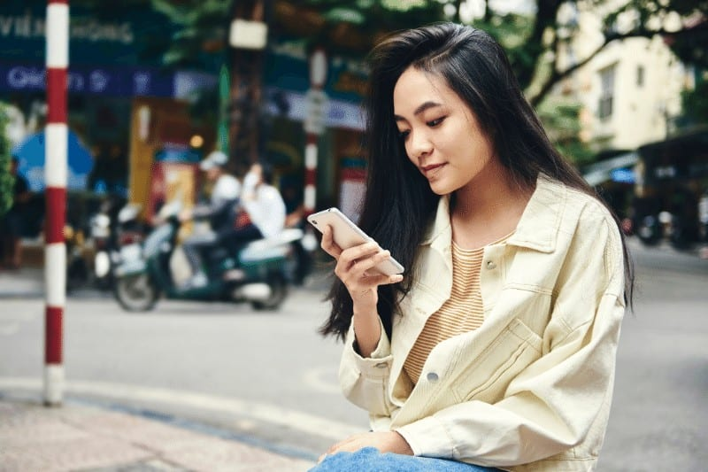 Asian woman scrolling on phone | modern-day idolatry